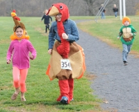 Dressed up in a turkey suit, East Vincent Elementary School sixth grader Jeanne Tokay encourages Avery Taylor who wears a turkey hat to keep on running as part of the turkey trot that was held at the school.