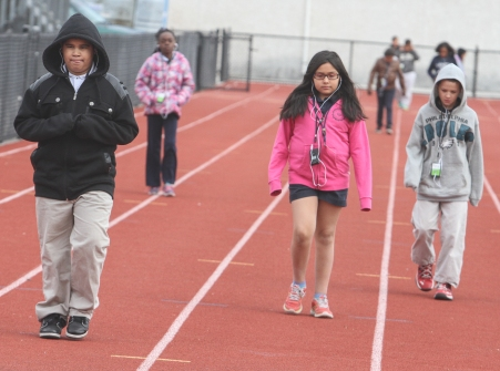 KEVIN HOFFMAN — THE MERCURY Fifth graders at Pottstown Middle School walk around the high school track while listening to their classroom lesson on MP3 players.