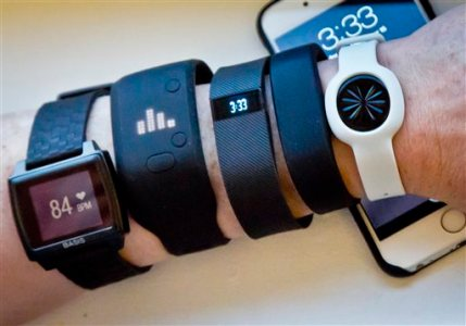 Fitness trackers, from left, Basis Peak, Adidas Fit Smart, Fitbit Charge, Sony SmartBand, and Jawbone Move, are posed for a photo next to an iPhone, Monday, Dec. 15, 2014, in New York. (AP Photo/Bebeto Matthews)