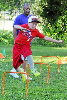 Robert Golden jumps the hurdles as he run the obstacle course as a Pottstown YMCA family fitness in the park event held at Memorial Park. Overseeing the event is YMCA sports coordinator Ken Trusty in background. Photo by John Strickler The Mercury