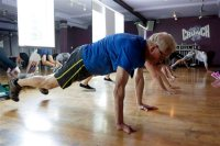 """In this Monday, Feb. 2, 2015 photo, Denis Kelly, 74, participates in a Cutthroat Cardio class at a Crunch Gym in Miami Beach, Fla. Crunch's latest workout is modeled after the T.V. show """"Cutthroat Kitchen"""". (AP Photo/Lynne Sladky)"""