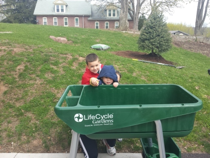 "Two children pose in front of a ""Garden on Wheelz"" cart at the Spring City Public Library. Over the summer, youth used the mobile carts to plant herbs in. The library is having a Farm to Table gala this Friday to help raise money for future programs."