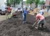 John Strickler - The Mercury Volunteers spread piles of soil on the new edible garden at 301 Walnut Street in Pottstown.