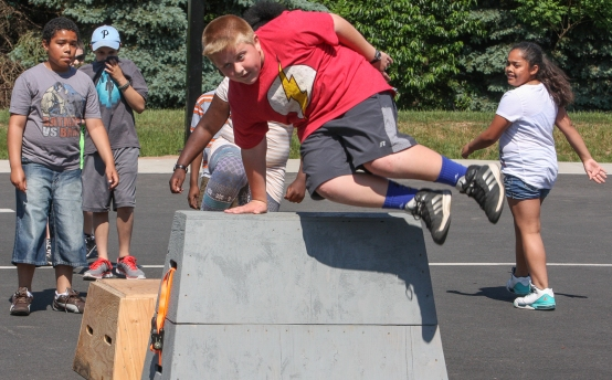 KEVIN HOFFMANÐTHE MERCURY This 4th. grade Rupert Elem. student leaps over a wooden block balancing on one hand.