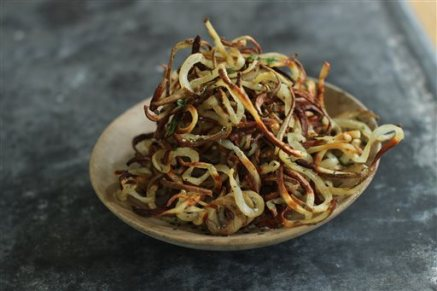 This Jan. 12, 2015 photo shows baked garlic thyme curly fries in Concord, N.H. This dish is from a recipe by Melissa d'Arabian. (AP Photo/Matthew Mead)