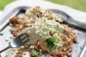 This June 8, 2015 photo shows grilled cauliflower steaks with lemon lime feta gremolata in Concord, N.H. Cauliflower is a veggie steak favorite, its flavor enhanced by the high heat of grilling or roasting, which coax out a sweet earthiness. (AP Photo/Matthew Mead)
