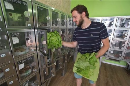 "In this July 2, 2015 photo, delivery man Michael Luminau puts greens in automat boxes in Paris, France. Joseph Petit employs no staff at his two Paris stores. Both called Au Bout du Champ - ""at the end of the field"" - the small spaces are stacked with metal lockers containing just-picked strawberries, hours-old eggs, and neat bunches of carrots or spring onions, depending on the season. Customers simply choose the box that contains the food they want to buy, then pay at a console to open the door. (AP Photo/Michel Euler)"