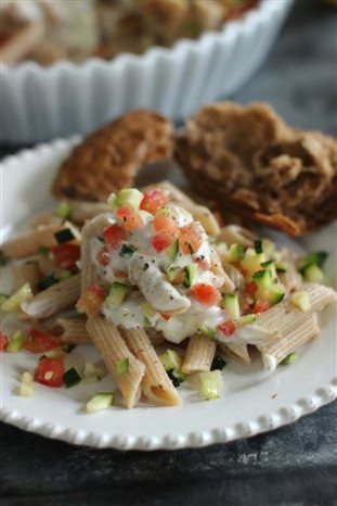 This June 15, 2015 photo shows penne pasta with tomatoes, zucchini and creme fraiche in Concord, N.H., a weeknight-friendly meal that is big on flavor, but not on labor. (AP Photo/Matthew Mead)
