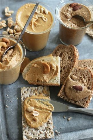This June 22, 2015 photo shows homemade nut butters from (from bottom clockwise) peanut butter, cashew butter and almond butter in Concord, N.H. This dish is from a recipe by Sara Moulton. (AP Photo/Matthew Mead)