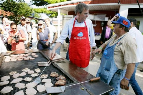 Republican presidential candidate, former Florida Gov. Jeb Bush, talks with Dana Wanken, right, as he works the grill in the Iowa Pork Producers tent during a visit to the Iowa State Fair, Friday, Aug. 14, 2015, in Des Moines, Iowa. (AP Photo/Charlie Neibergall)
