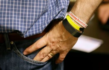 """FILE - In this July 31, 2015, file photo, Republican presidential candidate Wisconsin Gov. Scott Walker's fitness tracker is seen on his wrist as he meets with local residents at Tom and Tiff's diner in Glenwood, Iowa. Walker is counting steps on his FitBit. Jeb Bush swears by a paleo diet. Bobby Jindal is a self-proclaimed """"gym rat."""" With long travel days and a fresh slab of cherry pie never far away, the campaign trail is a notoriously unhealthy place to live. (AP Photo/Charlie Neibergall, File)"""