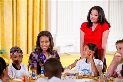 """First lady Michelle Obama, accompanied by Lets Move! Executive Director Deb Eschmeyer, right, talks with children in the East Room at the White House in Washington, Wednesday, June 3, 2015, after they helped prepare and eat food harvested from the White House Kitchen Garden with children from all over the country who participated in events with the """"Let's Move!"""" campaign. The """"Let's Move!"""" campaign, started by Michelle Obama seeks to combat the epidemic of childhood obesity and encourage a healthy lifestyle. (AP Photo/Andrew Harnik)"""