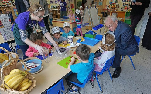 "The term ""farm to preschool"" encompasses efforts to serve local or regionally produced foods in early child care and education settings; provide hands-on learning activities such as gardening, farm visits, and culinary activities; and integrate food-related education into the curriculum. Here, USDA Undersecretary of Food, Nutrition, and Consumer Services Kevin Concannon participates in a hands-on lesson about local foods at a YMCA preschool in West Seattle, WA."