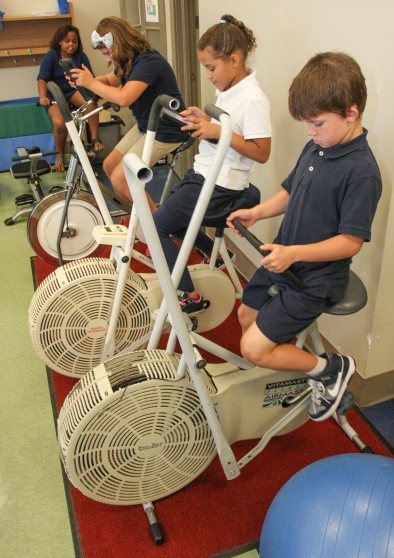Students at Rupert Elementary School ride stationary bicycles while looking over their lesson on iPad devices. Teachers in the Pottstown School District have found that students are more focused when they exercise while learning. KEVIN HOFFMAN — THE MERCURY