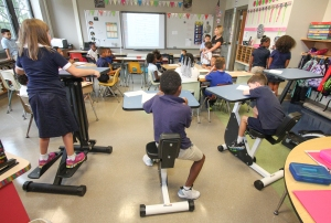 Students at Rupert Elementary School use kinesthetic desks in the classroom which allows them then to exercise while they learn . Some desks have pedals to resemble and bike and others resemble a strider exercise machine. KEVIN HOFFMAN — THE MERCURY