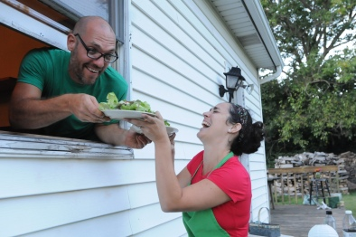 John Strickler - The Mercury David Ryle hands plates of fresh greens to his wife Wendy out of what he called the 'serving window' from the kitchen during the harvest dinner held out in the field at their home.