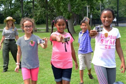 "This Aug. 24, 2015 photo released by the National Park Service shows fourth-graders on the grounds of Samuel W. Tucker Elementary School in Alexandria, Va., holding passes that give them and their families free admission for one year to all national parks, with ranger Kathy Kupper from the National Park Service at left. On Tuesday, Sept. 1, the National Park Service announced an initiative called ""Every Kid in a Park,"" which makes the annual $80 passes free for fourth-graders and their families. (AP Photo/National Park Service/Tami A. Heilemann)"