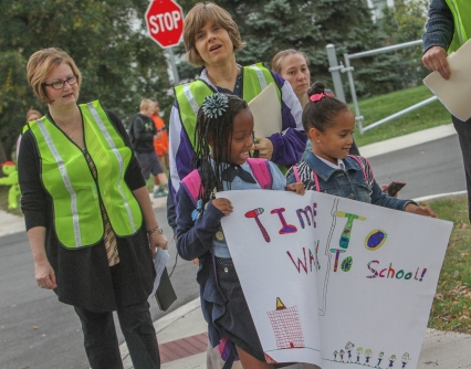 "Children hold up a ""Walk to School"" poster with adult volunteers behind them as they arrive at Rupert Elementary School Wednesday morning. Adults lead children to school as part of the walking school bus. KEVIN HOFFMAN — THE MERCURY"