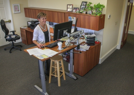 Rose Walters makes uses a standing desk in her office at the Pottstown Area Health & Wellness Foundation. She is able to stand or sit which makes for a better working health benefit in the office environment.  Kevin Hoffman - The Mercury