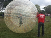 A boy walks in a giant hamster ball as part of fun fitness activity during the Upper Frederick Community Day on Saturday.