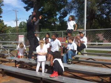 David Charles, standing to the left, motivates children as they get ready to perform a scene for a music video. Charles is the executive director of the STRIVE Initiative, a youth mentoring program.