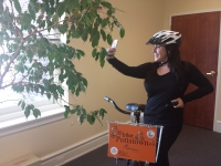 Skye Tulio, Pottstown Area Health & Wellness Foundation communications assistant, takes a selfie photo with her phone while she poses with a Bike Pottstown cruiser.