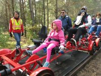 In this photo taken Thursday, Oct. 1, 2015, Adirondack Rail Explorers owner Alex Catchpoole gives instructions to riders preparing for a six-mile tour between Saranac Lake, N.Y. and Lake Clear. Claire Salabsky, 4, sits in the front seat while her parents, David and Angela Salabsky of Lancaster, Pa., and her 1-year-old sister, Grace, are behind her. Catchpoole launched the rail bike business in July, even as the state has proposed removing the deteriorated tracks to make way for a biking, hiking and snowmobile trail. (AP Photo/Mary Esch)