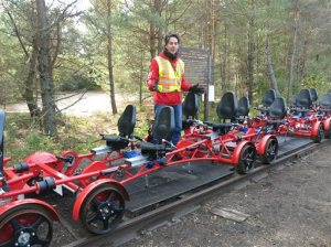 In this photo taken Thursday, Oct. 1, 2015, Adirondack Rail Explorers owner Alex Catchpoole gives instructions to riders preparing for a six-mile tour between Saranac Lake, N.Y. and Lake Clear. Catchpoole, 42, of Sidney, Australia, launched the rail bike business with his wife Mary-Joy Lu in July, even as the state has proposed removing the deteriorated tracks to make way for a biking, hiking and snowmobile trail. Lu said the rail bike enterprise had 10,000 riders at $25 apiece over the summer. (AP Photo/Mary Esch)