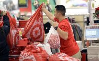 FILE - In this Nov. 23, 2012 file photo, a Target employee hands bags to a customer at the register at a Target store in Colma, Calif. Target executives on Wednesday, Sept. 16, 2015 said the company is handing out free Fitbit activity trackers to its more than 300,000 employees as the retailer tries to portray itself as a healthier place for both customers and workers. (AP Photo/Jeff Chiu, File)