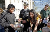 U.S. Surgeon General Vivek Murthy joins John C. Fremont High School students, including Xiaxiang English, left, at a display of food items grown from the school's Gardening Apprenticeship Program plot on the campus south of downtown Los Angeles Friday, Nov. 20, 2015. Murthy visited the partnership between community organizations and the high school to support healthy initiatives in neighborhoods starved for fresh produce and grappling with childhood obesity. Students involved in the 12-week after-school gardening apprenticeship program learn to grow food and cook healthy dishes, pulling from kumquat and lime trees and planters filled with potatoes, peas and beets.(AP Photo/Nick Ut)