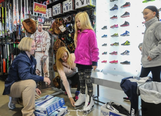 John Strickler - The Mercury Store manager Loretta Pavie, left assists Bobbi Nuss who was looking for new ice skates for her daughters Holli and Jana at the new Schuylkill Valley Sports store at Upland Square in West Pottsgrove Township.