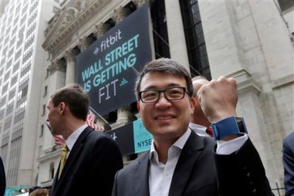 FILE - In a Thursday, June 18, 2015 file photo, Fitbit CEO James Park shows off one of his devices as he poses for photos outside the New York Stock Exchange, before his company's IPO. The company's app was the most downloaded on Apple Inc.'s app store on Christmas Day 2015, a sign that many people set up their Fitbit trackers after unwrapping them. It also suggests that Fitbit trackers were a hot seller during the holidays, despite increasing competition from Apple's smartwatch and others. (AP Photo/Richard Drew, File)