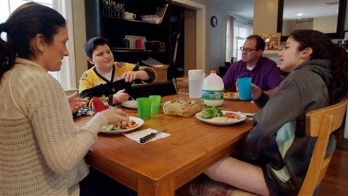 """This undated photo provided by Kikim Media shows the Scavotto family sitting down to dinner, in a scene from the documentary film, """"In Defense of Food."""" Anthony, second left, was referred to a program for overweight kids at Boston Children's Hospital after gaining 30 pounds in one year. The film is based on Michael Pollan's book, """"In Defense of Food,"""" and premieres on PBS on Dec. 30, 2015. (Brian Dowley/Kikim Media via AP)"""
