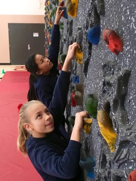 Holy Cross Regional School students Nina Nguyen and Elisabeth Wenstrup climb a rock wall during physical education class. The wall was transported to the school this August from Sacred Heart Parish in Royersford. Photo courtesy of Jennifer Phillips