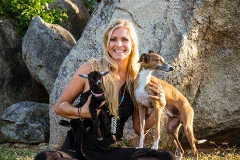 In this undated image released by Yoga Girl, fitness expert Rachel Brathen poses with her pets, Penny Lane, a goat, left and dog Ringo at her home in Aruba. Brathen is one of the new crop of hard-core trainers who have won legions of followers sharing their fitness tips on Instagram with their secrets for staying motivated all year long. (Ben Kane/Yoga Girl via AP)