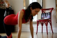 In this April 14, 2015 photo, Christina Macchiarola demonstrates how she uses the Crunch Live fitness app to work out in her apartment in New York. Crunch Live includes many of the workouts that earned the brand a devoted following and have been retired from their brick and mortar gyms.  (AP Photo/Seth Wenig)