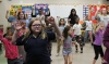 Students and their families wave their hands as they dance for fitness at Barth Elementary School during the first Wellness Night on Thursday.