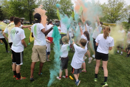 """People who participated in a color run use the last of the powder on one another after the race at West-Mont Christian Academy Saturday. The event raised money for the nonprofit organization """"In Ian's Boots"""" which provides shoes to those in need."""