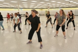 People move from side to side during a Zumba dance class at Coventry Mall. The mall offered the free fitness class with the purpose of increasing community engagement.