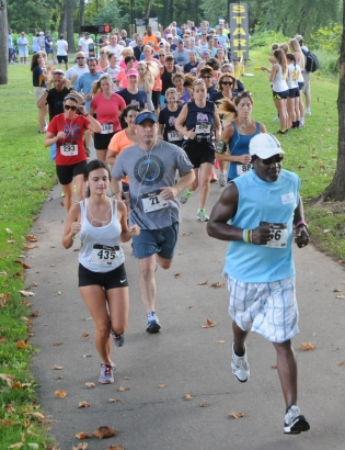 Vincent Artis at front right leads a group of runners at the start of the ACA 5k and 1 mile walk at Riverfront Park in Pottstown. The event was held in memory of Vincent and Kati Artis daughter Alexa C. Artis. Photo by John Strickler The Mercury
