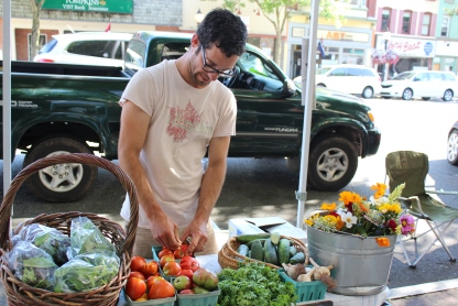 """Nathan Hasler-brooks of Tine & Toil Farm sells fresh produce and flowers during the outdoor farmers market in Pottstown last week. The market is open along High Street every Thursday from 4 to 8 p.m. until October. This week's theme for the market is """"Christmas in July."""""""