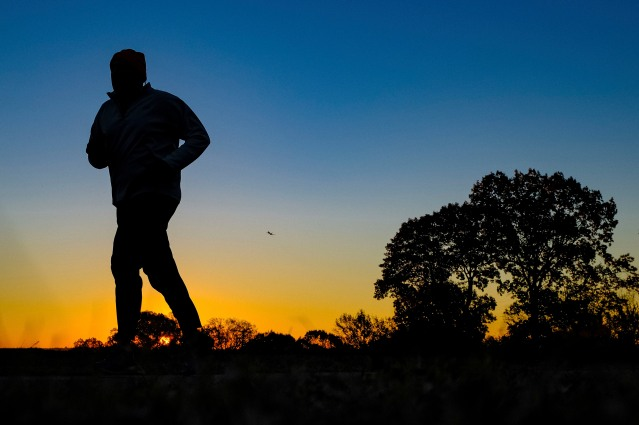 FILE - In this Tuesday, Nov. 22, 2016 file photo, a runner is silhouetted against the sunrise on his early morning workout near Arlington National Cemetery in Arlington, Va., across the Potomac River from the nation's capital. Research released on Monday, Jan. 9, 2017 suggests that people who pack their workouts into one or two days a week lower their risk of dying as much as those who exercise more often, as long as they get enough of it. (AP Photo/J. David Ake)